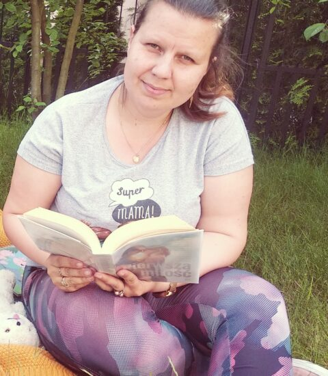 kobieta siedząca na trawie w rękach trzyma otwartą książkę