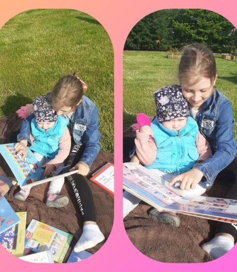 dwie dziewczynki siedzące na trawie, starsza trzyma książkę w rękach