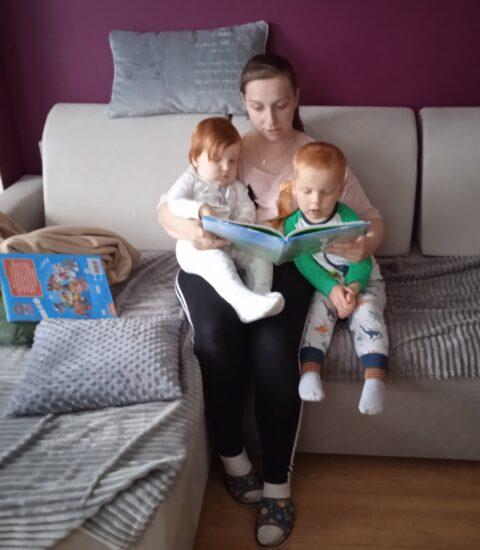 kobieta z dwójką dzieci na kolanach, w rękach trzyma książkę
