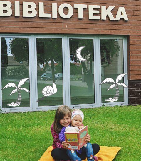 dwie dziewczynki siedzące na kocu przed budynkiem biblioteki, starsza trzyma książkę w rękach
