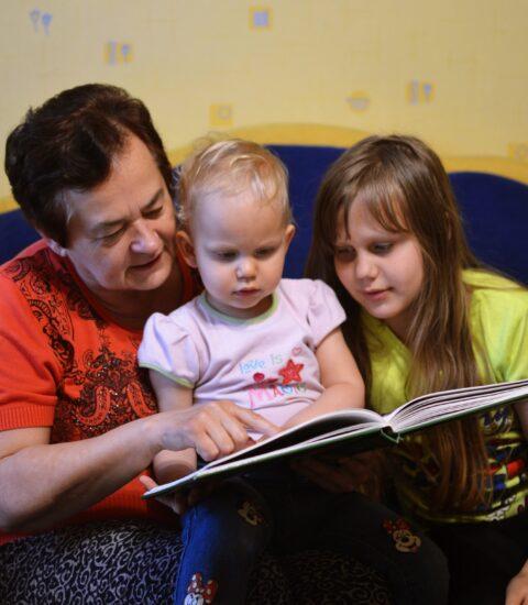 kobieta w czerwonej bluzce, dwie dziewczynki nad otwartą książką