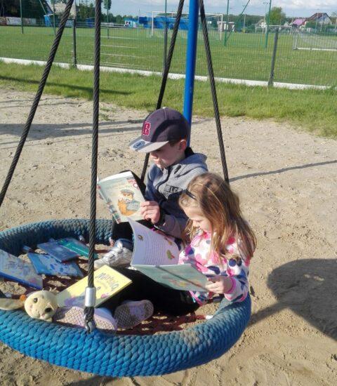 chłopiec z dziewczynką na huśtawce z książkami w rękach