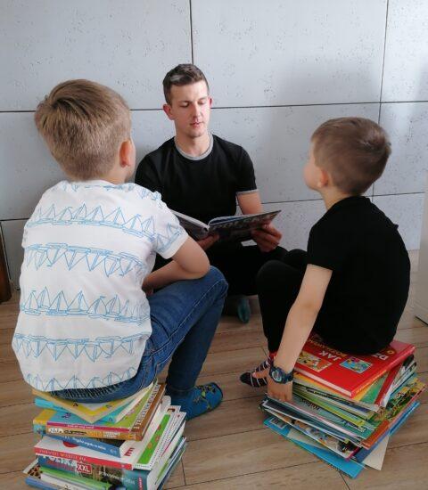 mężczyzna siedzi przodem do dwóch chłopców, trzyma otwartą książkę