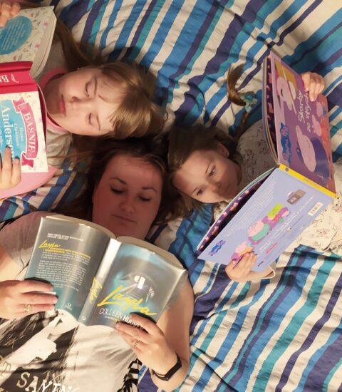 trzy osoby leżące z otwartymi książkami w rękach