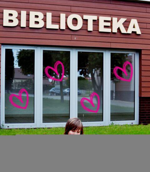 dziewczynka na kocu siedzi na trawie przed siedzibą biblioteki