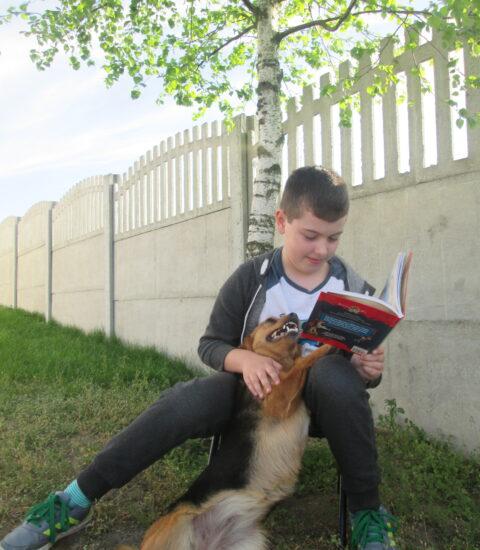 chłopiec siedzący pod drzewem, w rękach trzyma książkę, obok pies