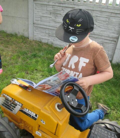 chłopiec w czapce zasłaniającej twarz klęczy przy traktorku, w ręku trzyma klucz i książkę