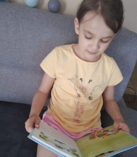 dziewczynka trzyma w rękach otwartą książkę
