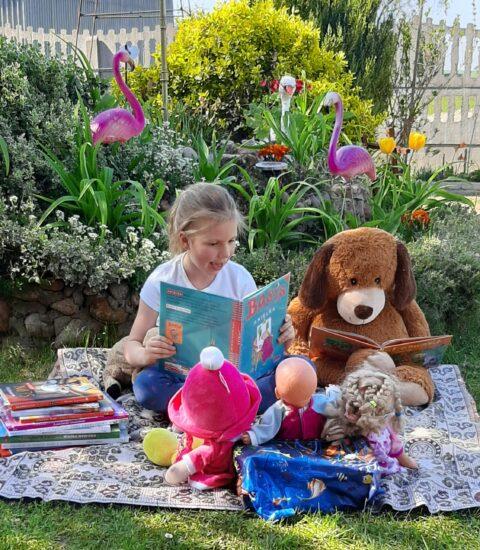 dziewczynka z książką siedzi na kocu w otoczeniu maskotek