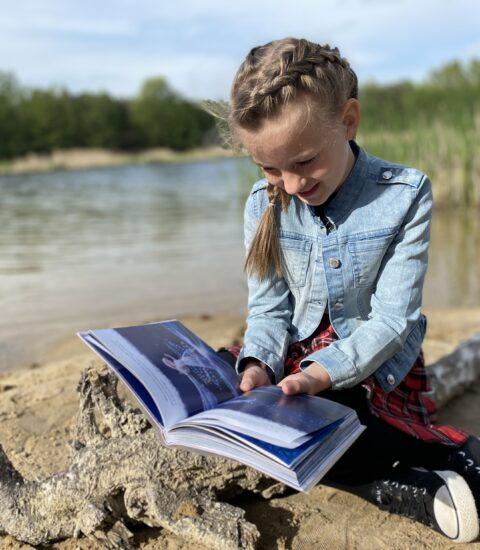 dziewczynka siedzi nad brzegiem jeziora w rękach trzyma książkę
