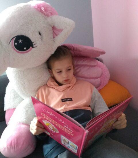 dziewczynka oparta o dużą maskotkę, w rękach trzyma książkę