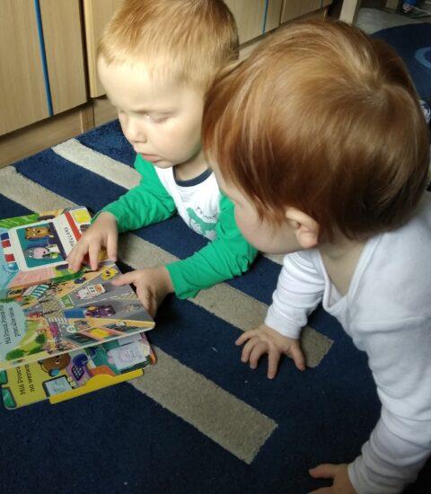 woje małych dzieci leżących na dywanie, oglądają książkę
