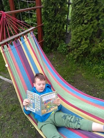 chłopiec na kolorowym hamaku, w rękach trzyma książkę