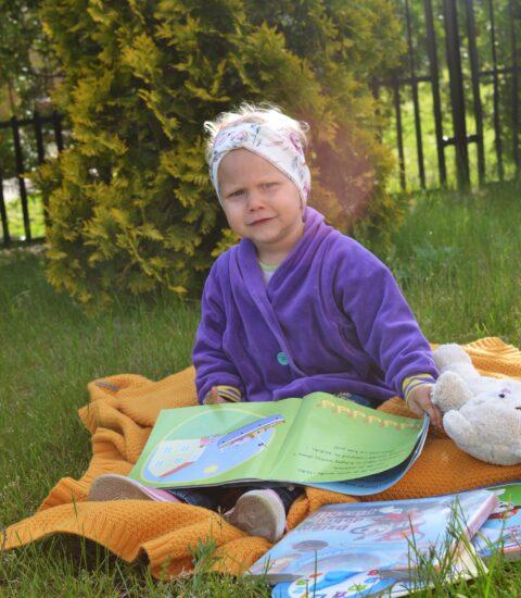mała dziewczynka siedząca na trawie, na kocu, przed sobą ma otwartą książkę