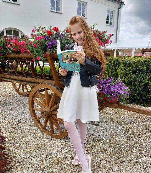 dziewczynka stoi, w rękach trzyma książkę, w tle drewniany wóz z kwiatami