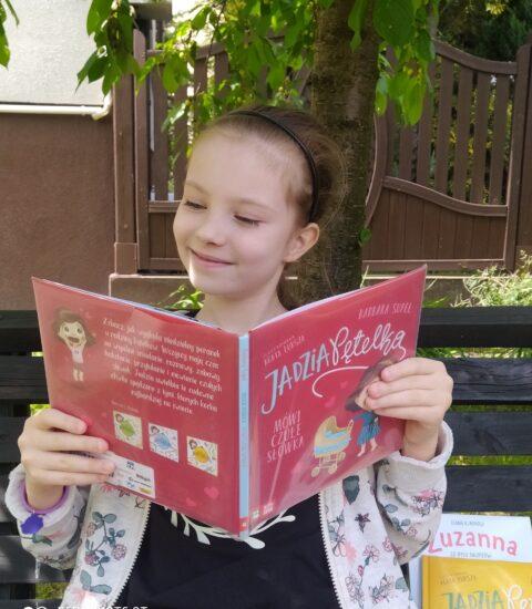 dziewczynka z otwartą książką w rękach siedzi pod drzewem