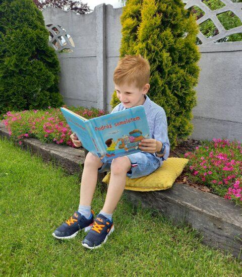 chłopiec siedzący w ogrodzie, czyta książkę