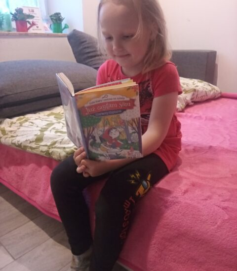 dziewczynka siedząca na łóżku, czyta książkę