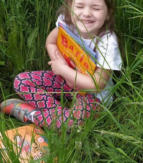 uśmiechnięta dziewczynka w trawie, tuli do siebie książkę