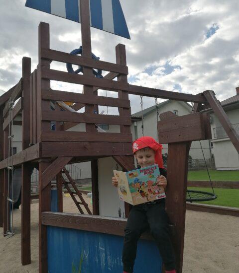 chłopiec ubrany w czapkę pirata na placu zabaw, w rękach trzyma książkę