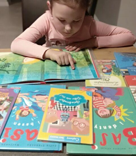 dziewczynka siedzi przy stole, czyta książkę
