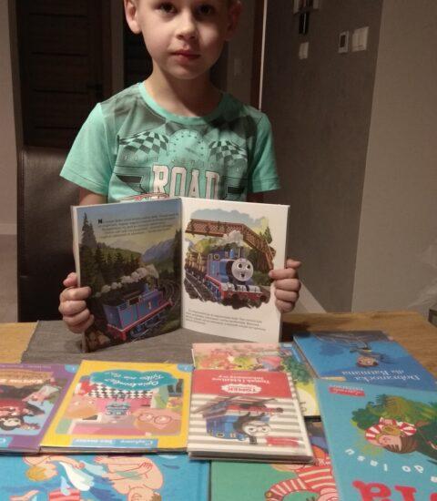 chłopiec stoi przed stołem, na którym są rozłożone książki