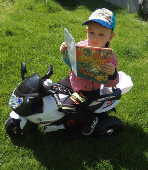 chłopiec na motorku z książką w rękach