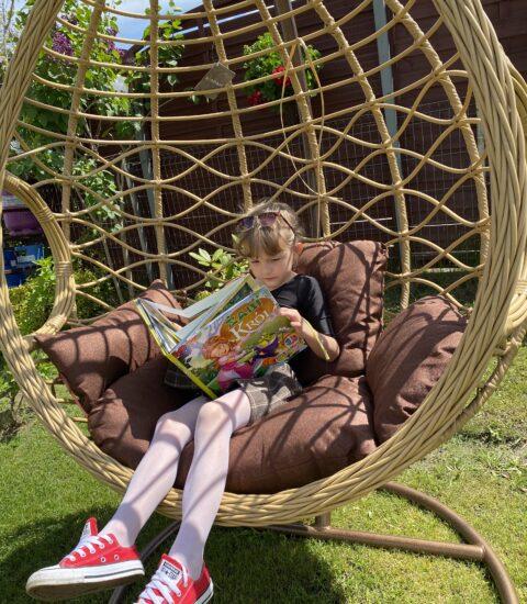 dziewczynka w fotelu ogrodowym siedzi z książką