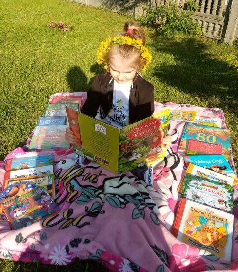 dziewczynka w ogrodzie wśród książek siedzi na kocu