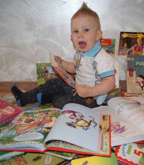 mały chłopiec siedzący na podłodze wśród książek