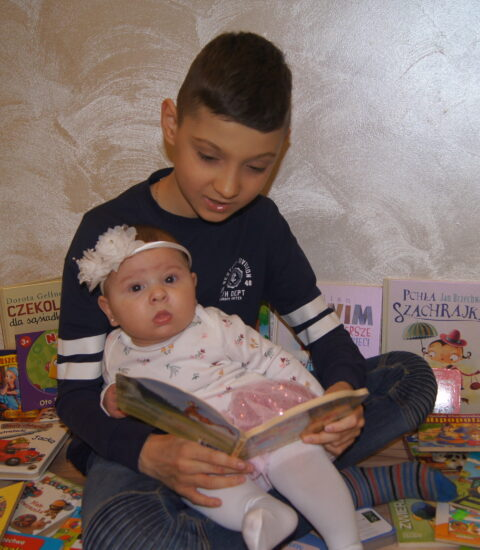 chłopiec siedzący na podłodze przed nim mała dziewczynka, chłopiec czyta książkę