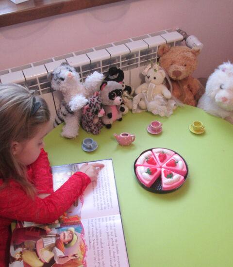 dziewczynka siedzi przy stoliku, czyta książkę