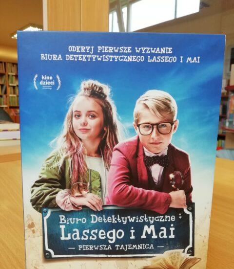 okładka płyty filmu. Postaci chłopca i dziewczynki opierające się na szyldzie z tytułem filmu Biuro Detektywistyczne Lassego i Mai