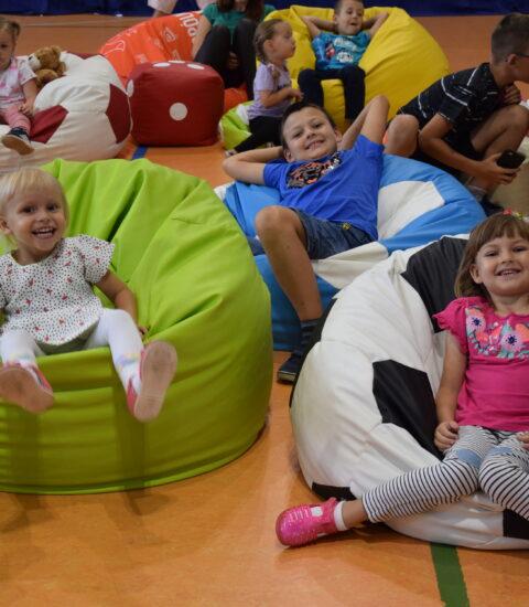 uśmiechnięte dzieci siedzą na kolorowych pufach