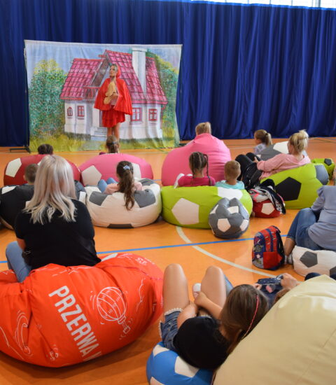 dzieci siedzą na kolorowych pufach, w tle aktorka w przebraniu Czerwonego Kapturka