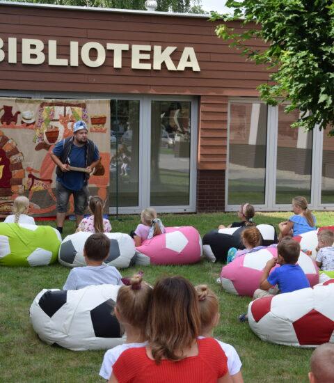 aktor z czapką na głowie pochylony w stronę publiczności, dzieci siedzą na kolorowych pufach