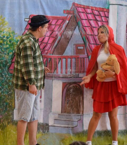kobieta przebrana za Czerwonego Kapturka, w ręku trzyma pluszową zabawkę, obok stoi mężczyzna w koszuli w kratę mężczyzna przebrany za wilka, opiera się o laskę