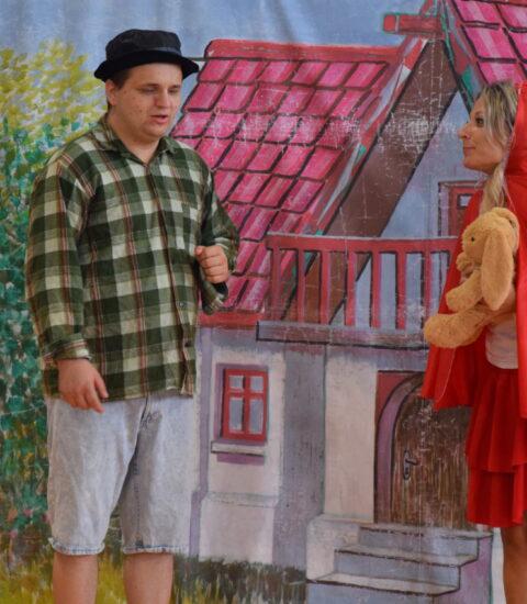 mężczyzna ubrany w koszulę w kratę stoi na tle kurtyny imitującej dom, obok kobieta w przebraniu Czerwonego Kapturka