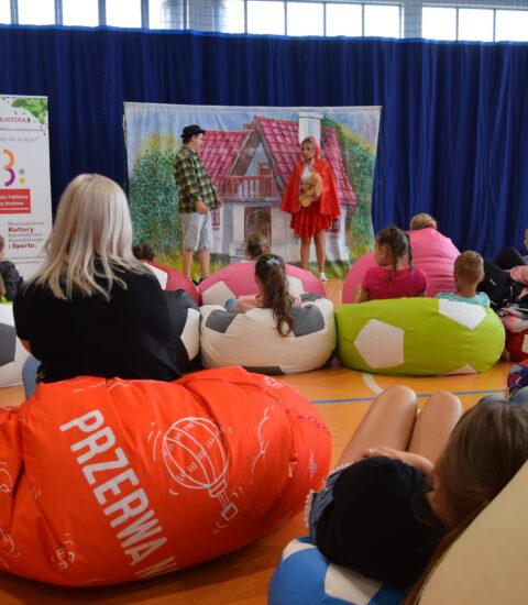 dzieci siedzą na kolorowych pufach, w tle aktorka w przebraniu Czerwonego Kapturka i mężczyzna w koszuli w kratę