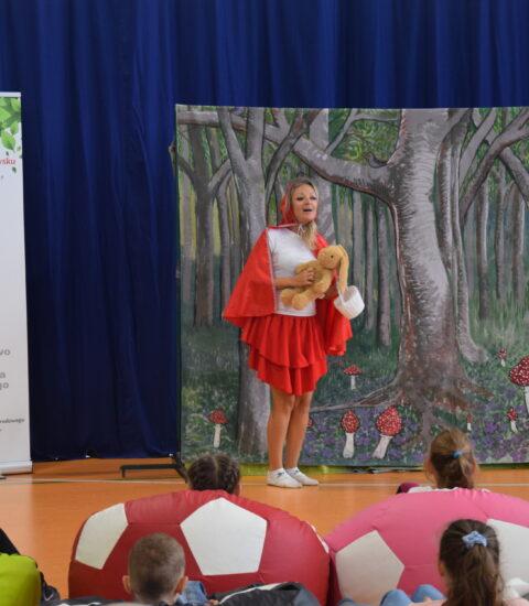 aktorka w przebraniu Czerwonego Kapturka stoi na tle imitacji lasu, w rękach trzyma pluszową zabawkę