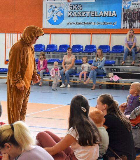 mężczyzna w przebraniu niedźwiedzia stoi przodem do publiczności