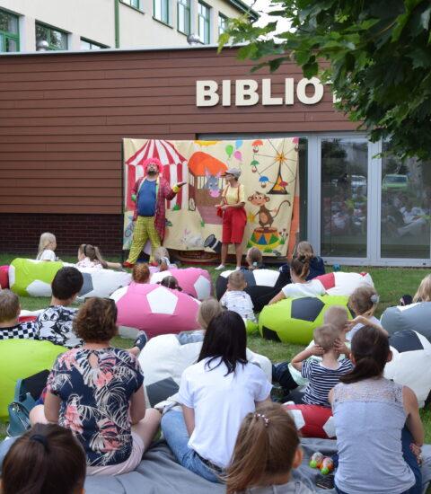 aktorzy w przebraniach na tle ścianki teatralnej, zwróceni w stronę dzieci siedzących na kolorowych pufach gestykulują