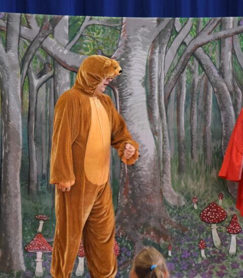 mężczyzna w przebraniu niedźwiedzia stoi na tle imitacji lasu, obok kobieta w przebraniu Czerwonego Kapturka