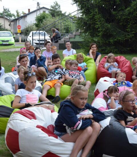 dzieci i dorośli siedzą na kolorowych pufach, na trawie