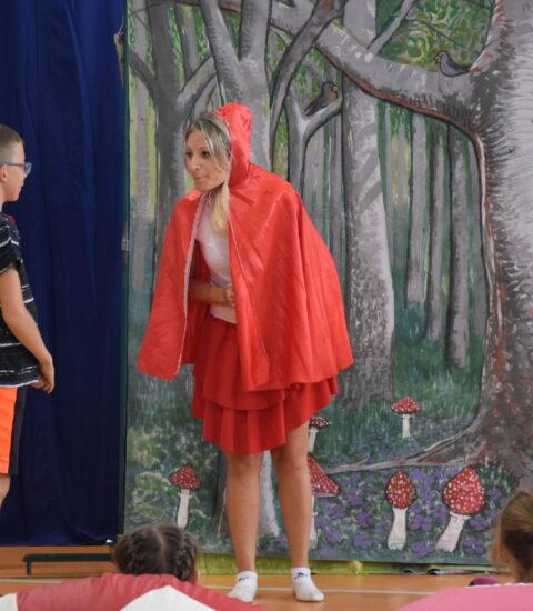 aktorka w przebraniu Czerwonego Kapturka stoi na tle imitacji lasu pomiędzy chłopcem a dziewczynką