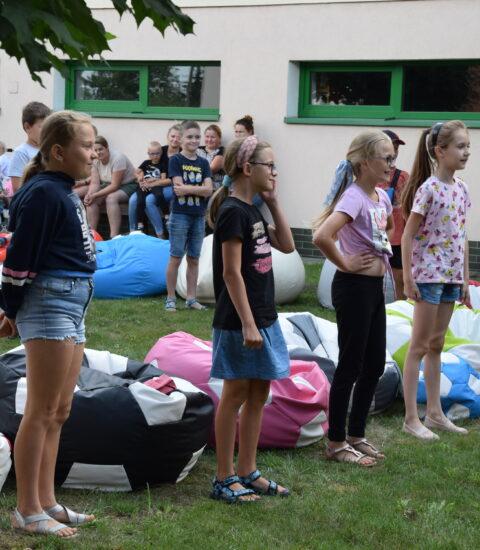 dzieci i dorośli siedzą na kolorowych pufach, w pierwszym rzędzie dziewczynki stoją