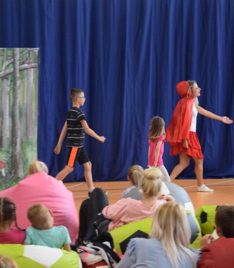 aktorka w przebraniu Czerwonego Kapturka razem z chłopcem i dziewczynka maszerują