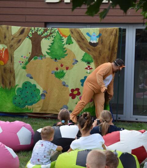 aktor w pomarańczowym kostiumie zagląda za teatralną ściankę
