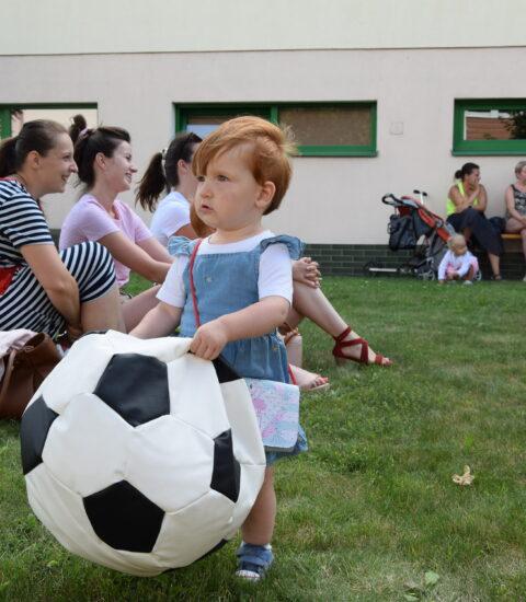 mała dziewczynka trzyma w rękach kolorową pufę, w tle uśmiechnięci dorośli