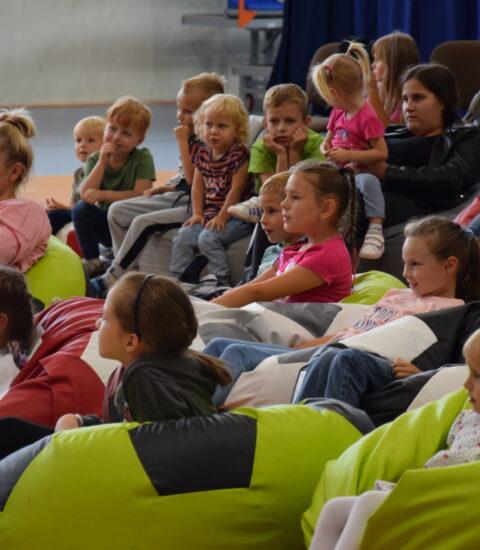 dzieci siedzą na kolorowych pufach